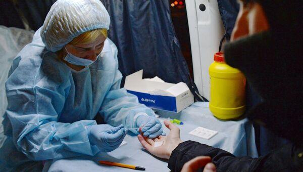 Медицинский работник производит экспресс-анализ крови. Архивное фото