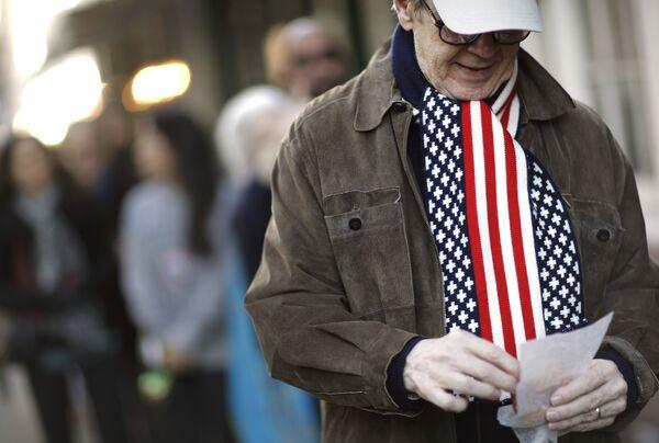 Мужчина в шарфе под цвет флага США на избирательном участке в Нью-Йорке