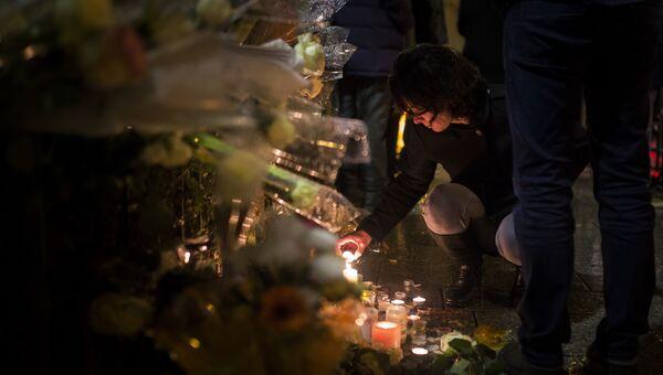 Женщина зажигает свечу у Батаклана перед концертом Стинга. 12 ноября 2016 год. Архивное фото