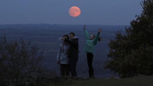 Семья фотографируется на фоне луны, Лафборо, Великобритания. 13 ноября 2016