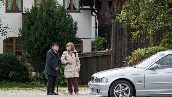 Пожилые люди рядом с автомобилем