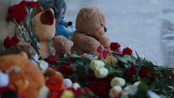 Цветы и игрушки у здания СДЮСШОР Сибиряк в Нефтеюганске в память о погибших в автокатастрофе на трассе Тюмень — Ханты-Мансийск