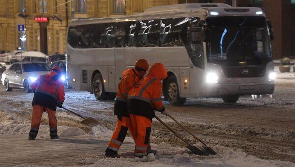 Сотрудники коммунальных служб убирают на улице снег во время снегопада в Москве. Архивное фото