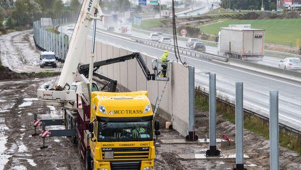 Рабочие возводят стену против незаконных мигрантов в Кале, Франция