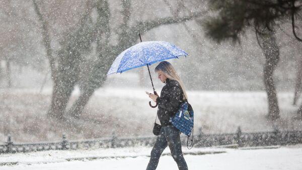 Девушка с зонтом во время снегопада на одной из улиц Симферополя