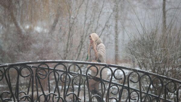 Девушка на одной из улиц Симферополя во время снегопада