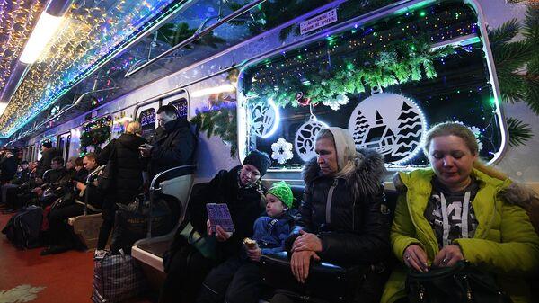 Пассажиры в новогоднем поезде Московского метро