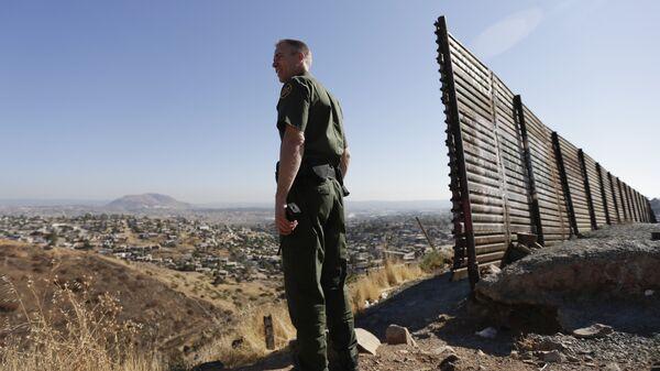 Сотрудник правоохранительных органов США у стены на границе США и Мексики в Сан-Диего. Архивное фото
