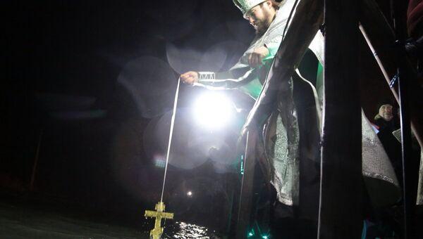 Священник проводит молебен и освящение воды перед крещенским купанием в источнике Красных пещер в Симферопольском районе Крыма