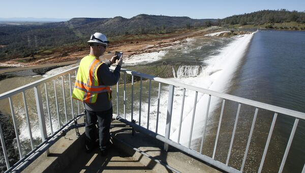Мужчина фотографирует плотину в городе Оровилл, штат Калифорния, США. 11 февраля 2017