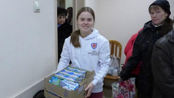 Наталья Сивцова, активистка Союза добровольцев России, участвует в раздаче молочных продуктов малоимущим в ЦСО Щукино. Москва, 16 февраля 2017 г.