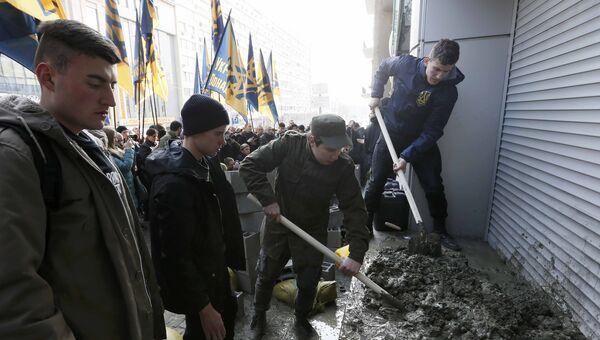 Представители Гражданского корпуса, созданного на базе Азова, замуровывают вход в отделение дочки российского Сбербанка в Киеве, Украина. 13 марта 2017