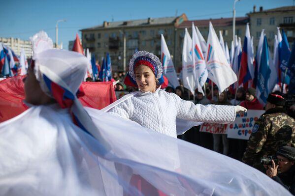 Участники представления во время митинга в честь третьей годовщины воссоединения Крыма с Россией в Омске