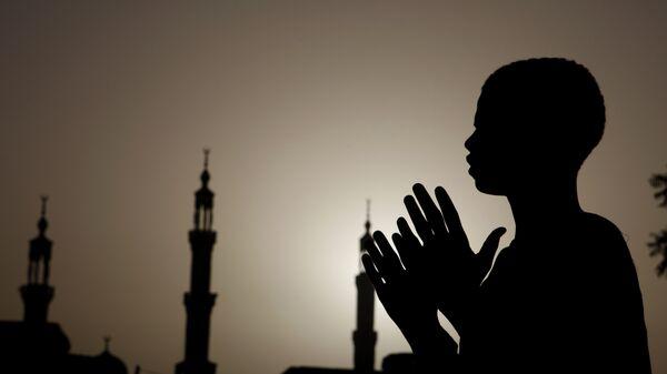 Суданский мальчик молится у мечети в Хартуме