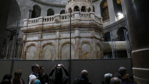 Посетитель фотографирует отреставрированную Кувуклию в храме Гроба Господня в Иерусалиме