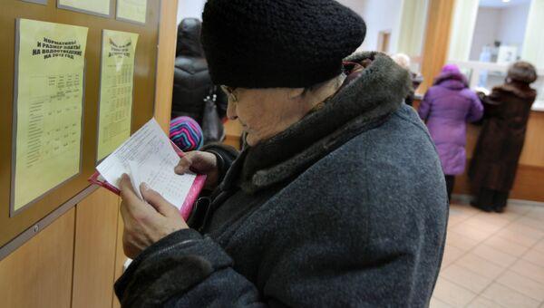 Женщина проверяет правильность заполнения квитанций об оплате коммунальных услуг