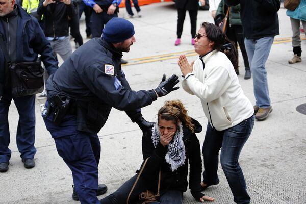 Сотрудник полиции освобождает протестующую во время столкновений между сторонниками и противниками Американо-израильского комитета по общественным связям в Вашингтоне