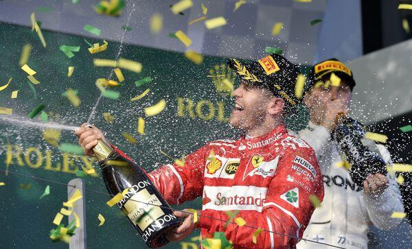 Немецкий автогонщик Себастьян Феттель празднует победу в гонке в Мельбурне