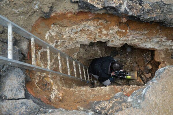Видеооператор в подземной комнате, обнаруженной археологами у основания Китайгородской стены в Москве