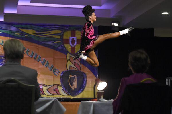 Танцовщица выступает перед судейской коллегией во время чемпионата мира по ирландским танцам в Дублине. Ирландия, 11 апреля 2017