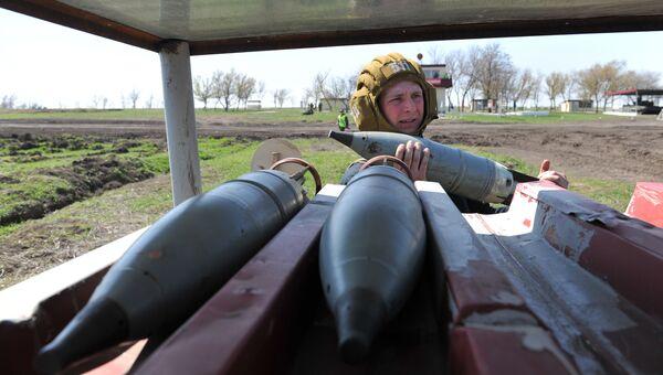 Танкист 150-й мотострелковой дивизии производит заряжение снарядов для танков перед началом учебных стрельб на полигоне Кадамовский в Ростовской области