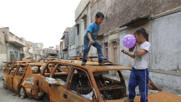 Дети играют на сожженных автомобилях в Мосуле. Архивное фото