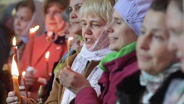 Прихожане радуются благодатному огню на праздничном пасхальном богослужении в храме Христа Спасителя в Москве