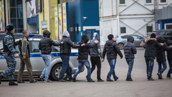 Сотрудник полиции ведет задержанных во время рейда на территории торгового-ярмарочного комплекса Москва в Люблино