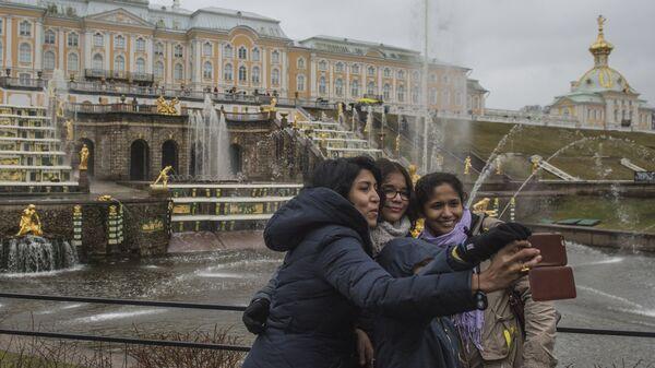 Туристы фотографируются на фоне фонтанов Большого каскада во время открытия нового летнего сезона в Государственном музее-заповеднике Петергоф