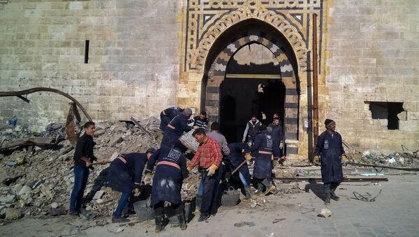 Горожане во время уборки на улице в районе Аль Назирия в сирийском Алеппо. Архивное фото