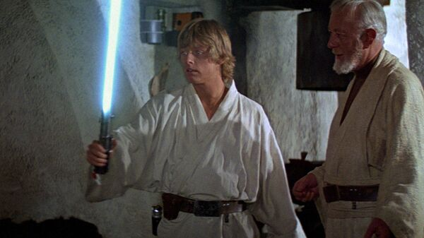 Люк Скайуокер держит в руках световой меч. Кадр из фильма