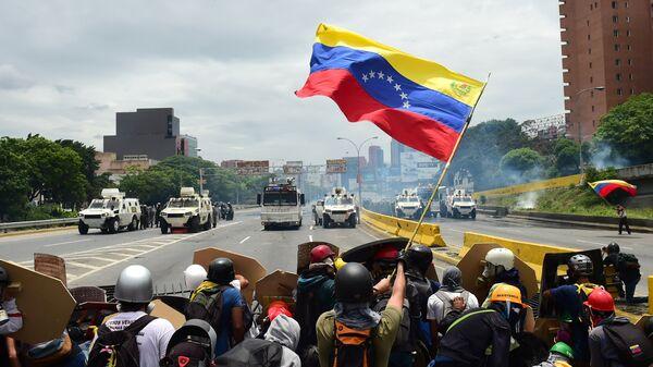 Представители оппозиции размахивают национальным флагом Венесуэлы в знак протеста против президента Николаса Мадуро в Каракасе. Венесуэла, 3 мая 2017