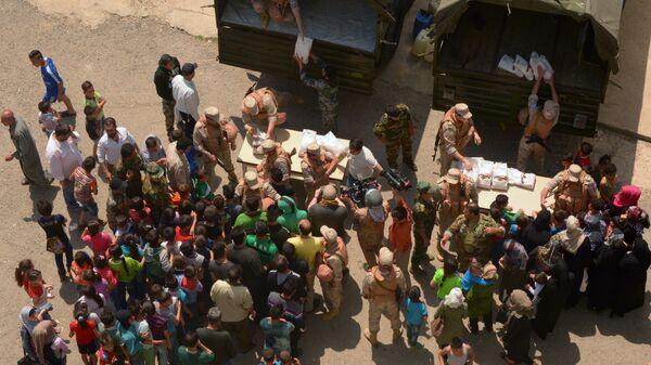 Раздача гуманитарной помощи офицерами Центра по примирению враждующих сторон в Сирии. Архивное фото