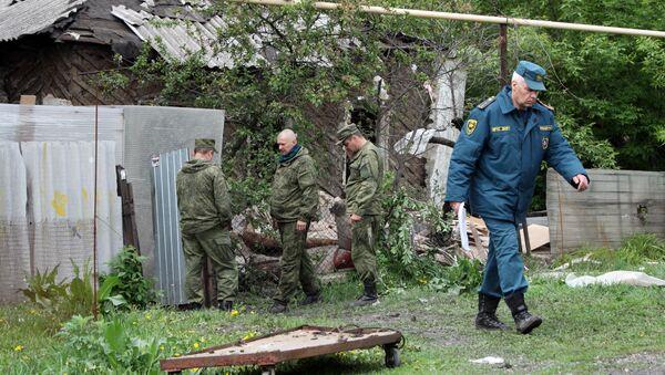 Сотрудники МЧС ДНР осматривают место артиллерийского обстрела Куйбышевского района Донецка