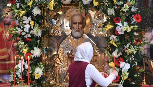 Женщина зажигает у свечи у иконы святителя Николая Чудотворца в храме Христа Спасителя, где находится ковчег с его мощами