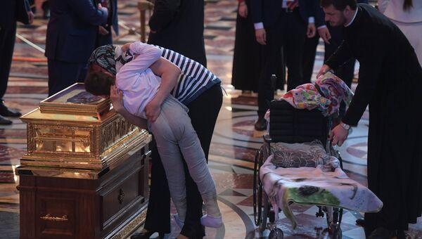 Женщина прикладывает ребенка к ковчегу с мощами святителя Николая Чудотворца в храме Христа Спасителя в Москве