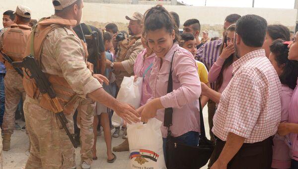Офицеры российского Центра по примирению враждующих сторон в Сирии раздают гуманитарную помощь жителям деревни Мшейрфа провинции Латакия. Архивное фото