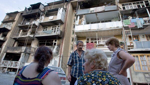 Жители Цхинвала возле своего дома, пострадавшего от пуль и снарядов в ходе обстрелов. 14 августа 2008 года