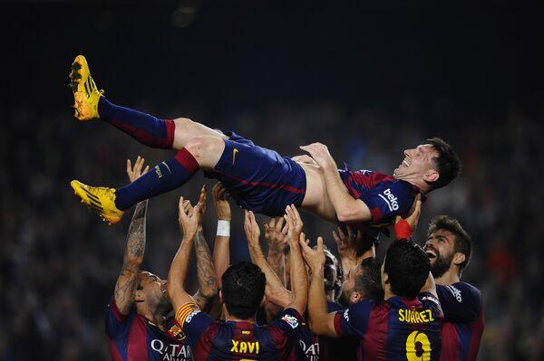 Нападающий футбольного клуба Барселона Лионель Месси с товарищами по команде после победы над Севильей