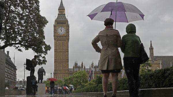 Прохожие у здания Парламента в Лондоне