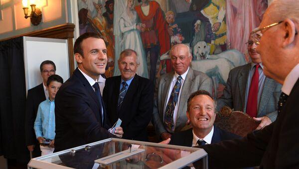 Президент Франции Эммануэль Макрон пожимает руку официальному лицу на избирательном участке. 18 июня 2017