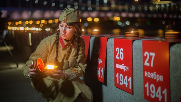 Участница патриотической акции Линия памяти зажигает свечу на Крымской набережной вдоль Москвы-реки в память о погибших в Великой Отечественной войне
