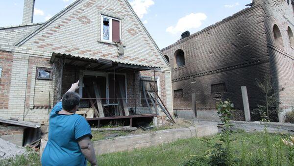 Местная жительница возле дома, пострадавшего от минометного артобстрела поселка Александровка в Донецкой области. 22 июня 2017