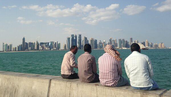 Мужчины сидят на набережной в Дохе, Катар