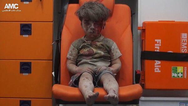 Пострадавший при обстреле Алеппо сирийский мальчик Омран. 17 августа 2017
