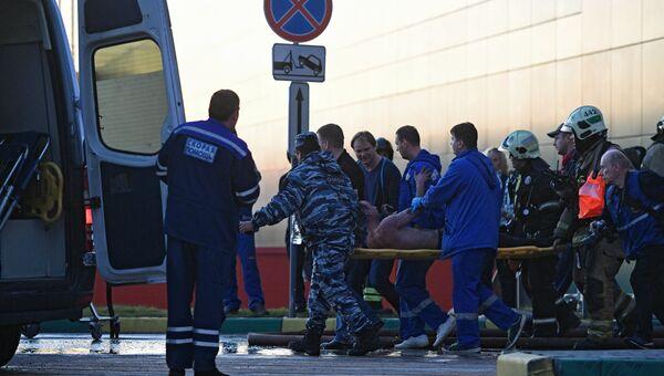 Сотрудники медицинской службы эвакуируют пострадавшего с места пожара в здании торгового центра РИО на Дмитровском шоссе в Москве