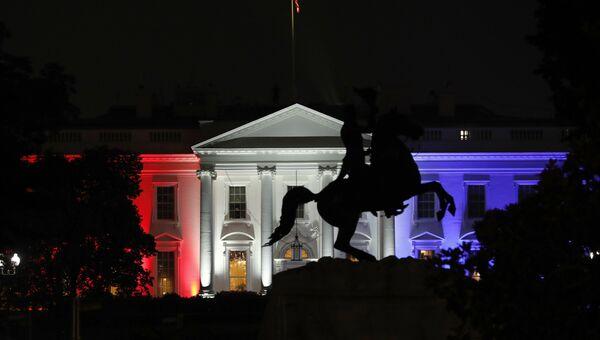 Северное крныло Белого дома освещеное красными, белыми и синими огнями