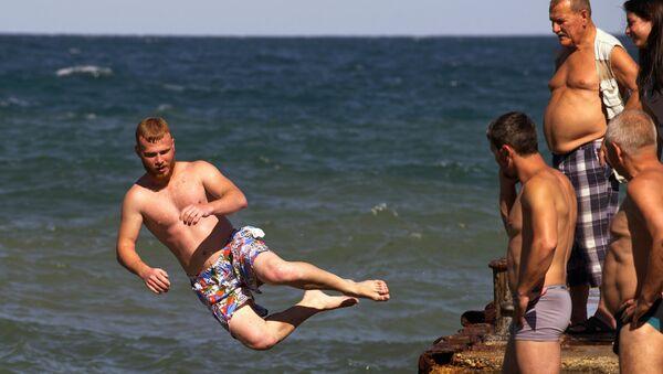 Отдыхающие прыгают с пирса в поселке Партенит
