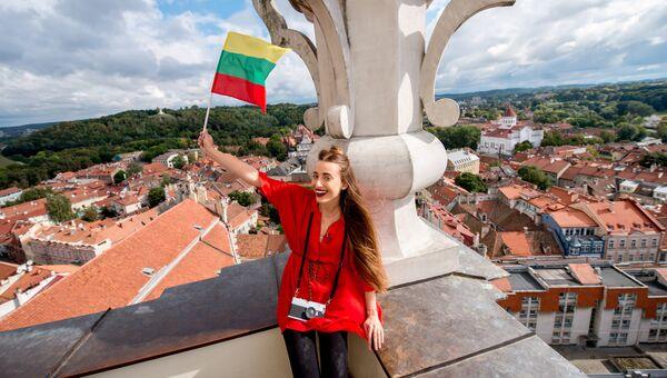 Девушка позирует с флагом Литвы на фоне Вильнюса. Архивное фото