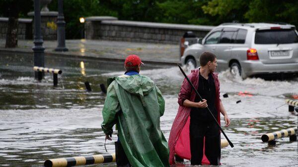 Работники коммунальной службы открывают решетки ливневой канализации на улице во Владивостоке